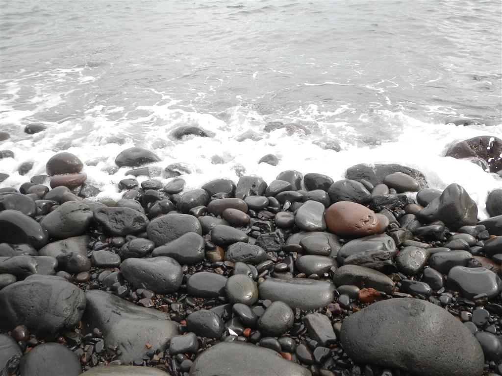 Bei der Wanderung kann man runter zum Strand laufen, die Steine sind pechschwarz.