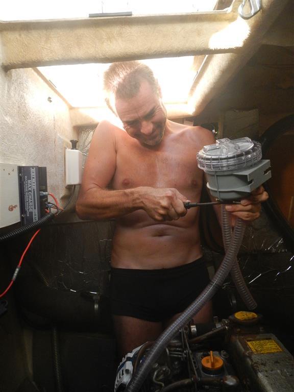 Sven baut den aus Deutschland mit gebrachten neuen Wasserfilter für die Backbordmaschine ein